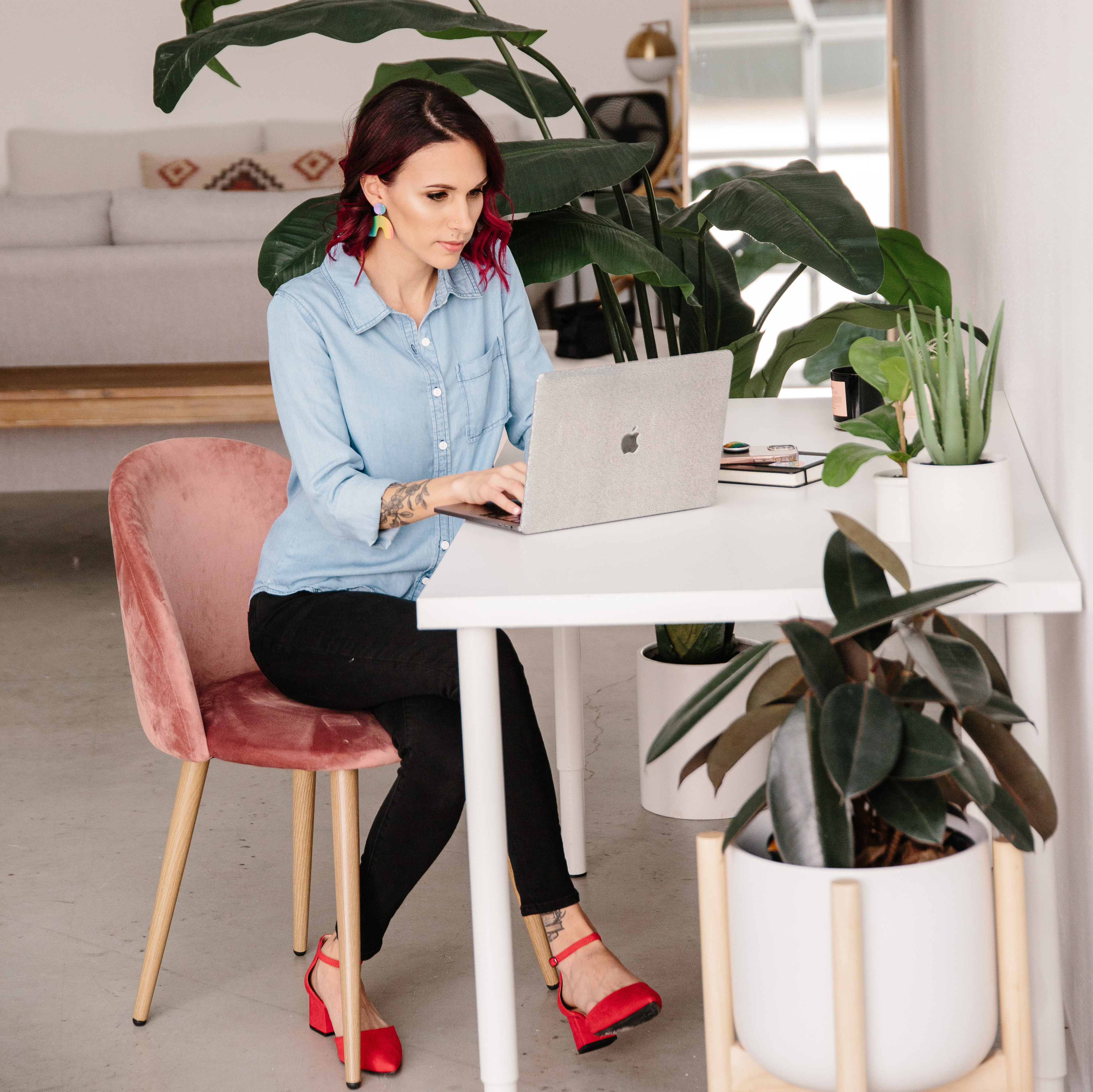 Shohreh sits in a blush-colored chair working at her laptop wearing bright red shoes, black pants, and a  light-colored chambray shirt