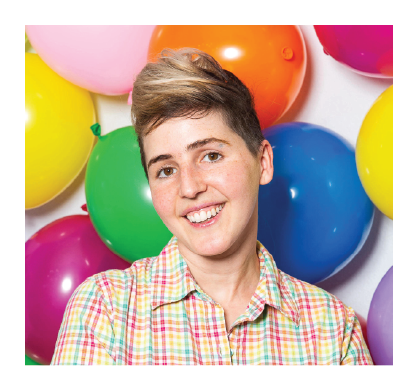 Shohreh's client, Abi, wears a rainbow plaid collared shirt and smiles against a background of colorful balloons