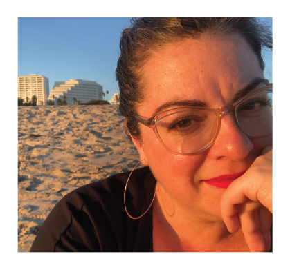 Shohreh's client Kate smiles wearing red lipstick and light glasses with one hand resting on her chain. Sand can be seen behind her.