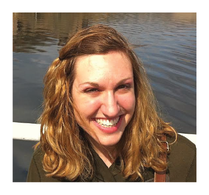 Shohreh's client Sarah smiles in front of a body of water. She has collar-bone length blonde hair and is wearing an olive-colored jacket.