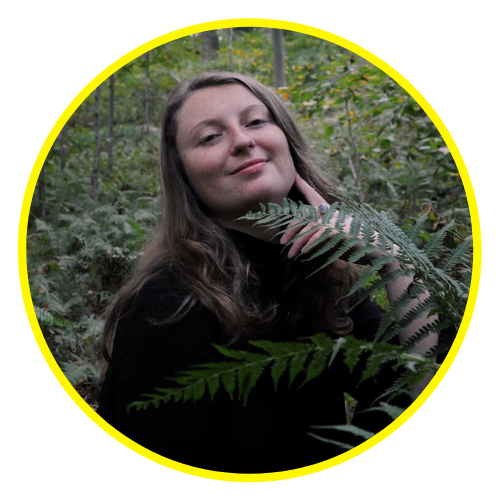 Eryn stands in a forest in a black turtle neck with flowy long hair. There are two green ferns directly in front of her.