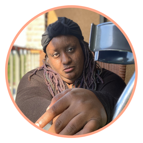 Imani looks directly at the camera. She wears a brown shirt and black wrap around the top of her head. Her hands and one of her crutches take up a large part of the frame