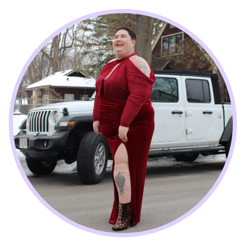 Chaya is pictured standing in front of a white jeep wearing a long-sleeved, deep-red velvet gown with a leg slit and shoulder cutouts
