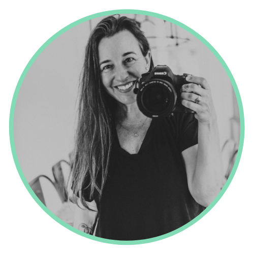 A black and white photo of Danielle smiling and holding up a Canon camera by her face